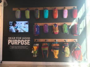 A backpack display on the right front wall of the Cotopaxi store.
