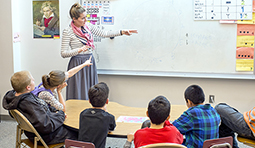 A U graduate student teaches students a music principle. Photo from U Piano Outreach website.
