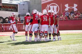 University of Utah Offense huddles to hear the next play call.