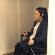 A patient doing a hearing test in a sound booth.